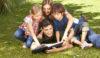 Glückliche Familie gemeinsam beim Lesen von einem Buch im Garten